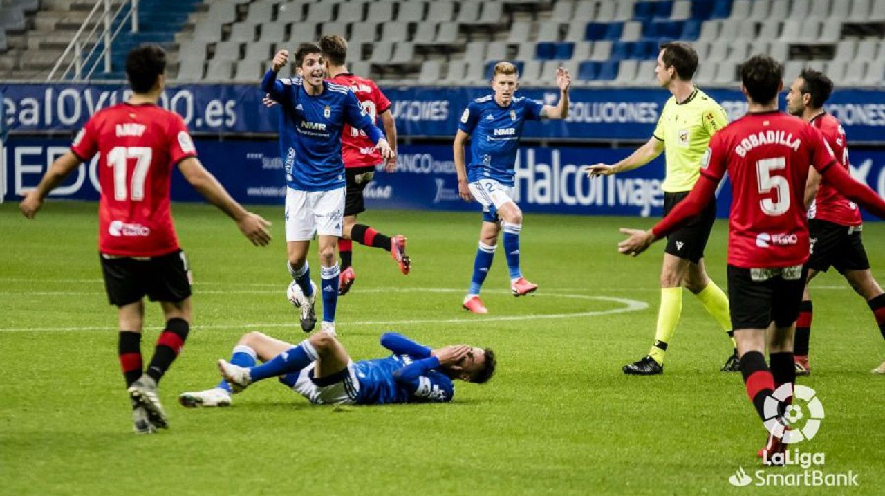 Edgar, con Tejera en el suelo, protesta al árbitro durante el Oviedo-Logroñés