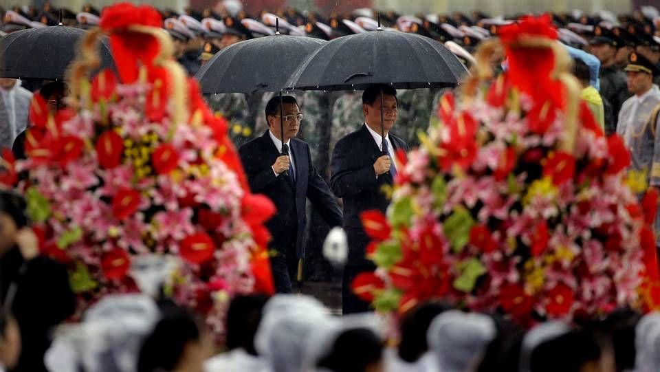 El presidente de China Xi Jimping y el primer ministro, Li Keqiang, llegan con paragüas a la ceremonia de los Héroes.