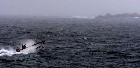 Una planeadora con mariscadores a bordo intenta seguir su camino en el litoral aguiñense pese a la crudeza del temporal.