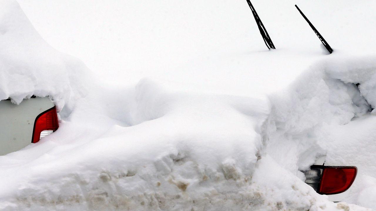 Carretera abierta alrededor de la nieve en Somiedo.Dos vehículos cubiertos de nieve, en el pueblo asturiano de Pajares.
