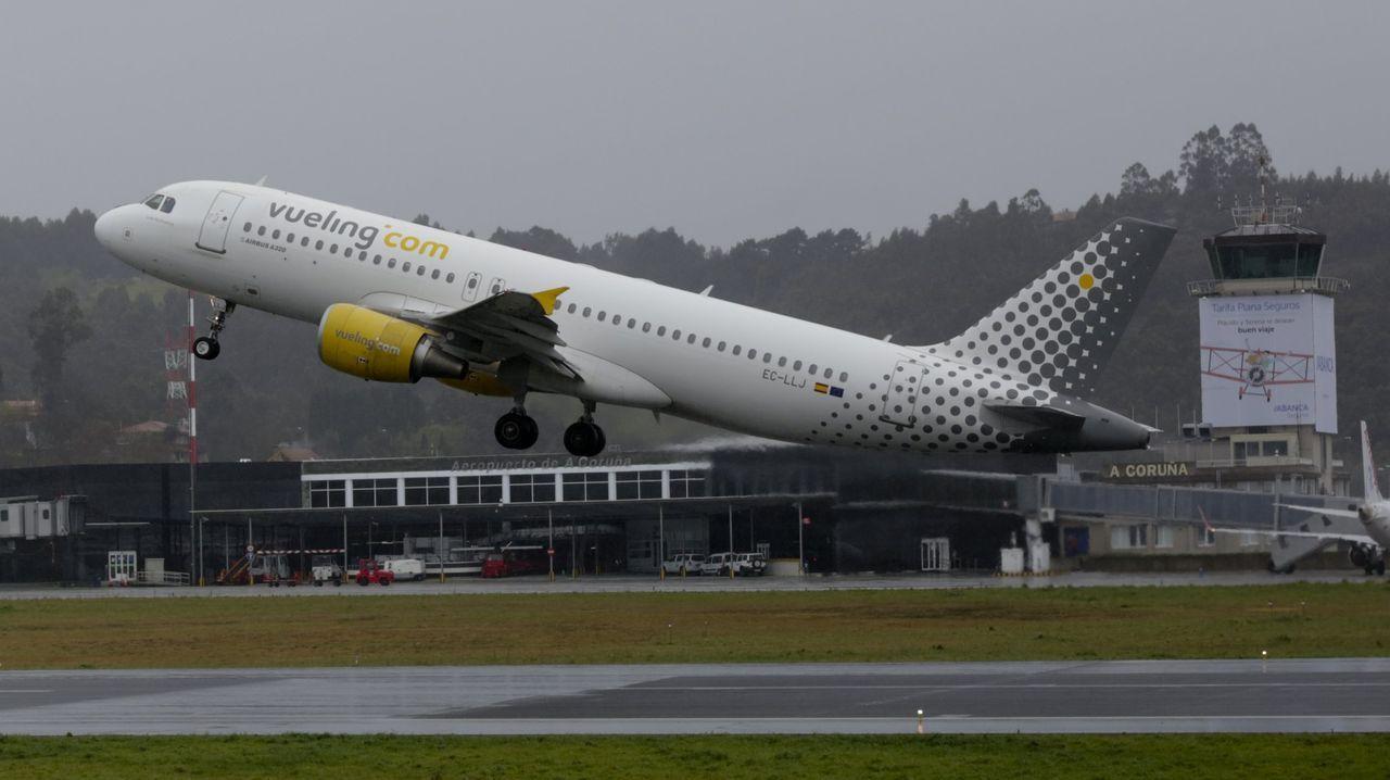 Un grupo de pasajeros consulta los vuelos en el Aeropuerto de Asturias.Imagen de archivo de un avión de Iberia