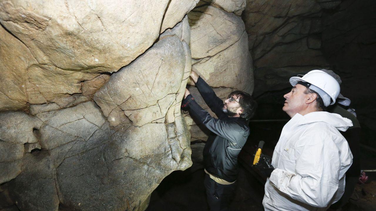El conselleiro de Cultura, Román Rodríguez ?a la derecha?, observa las muestras de arte rupestre de Cova Eirós en una visita que realizó a la cueva de Triacastela en el 2018