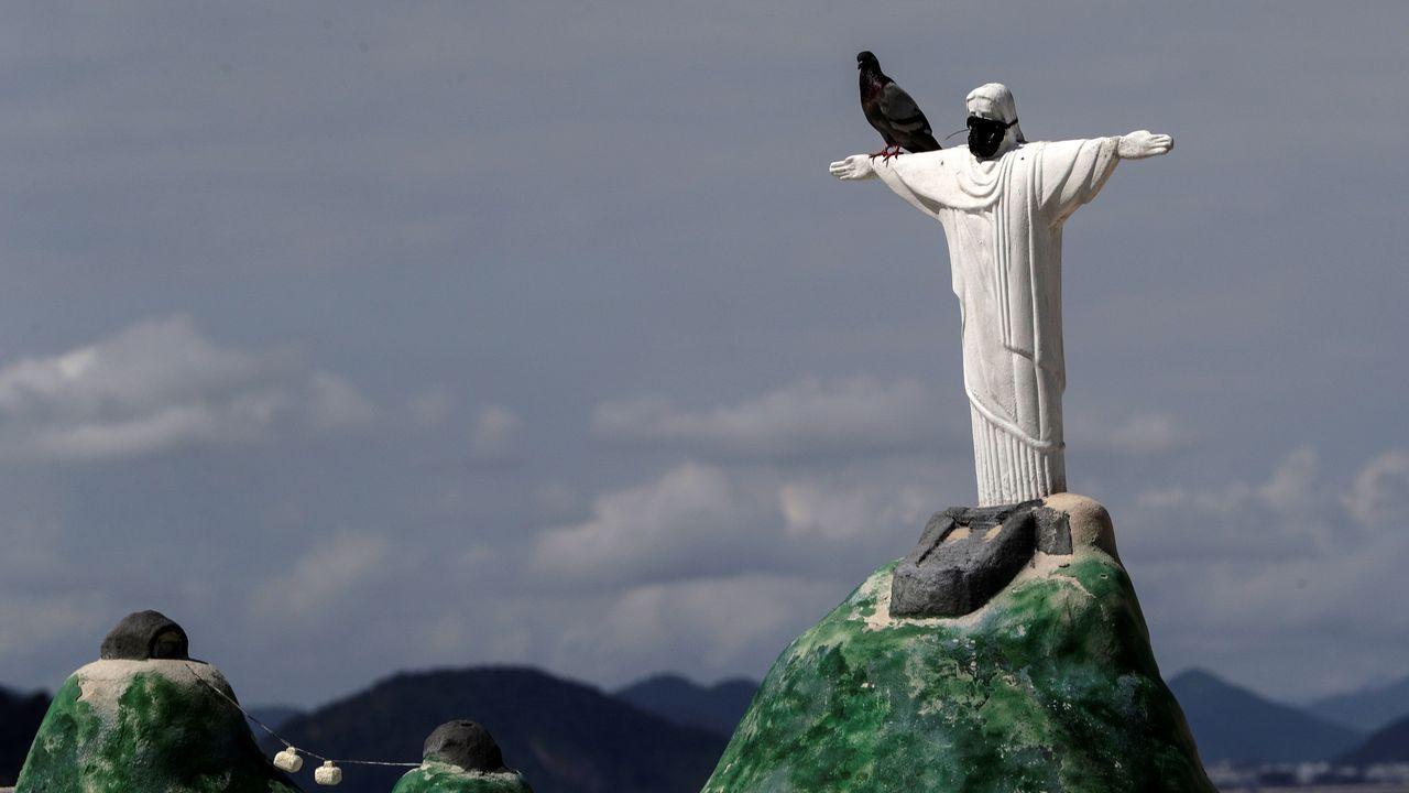 Vista de una estatua del Cristo Redentor de arena, con una mascarilla en Río de Janeiro (Brasil)