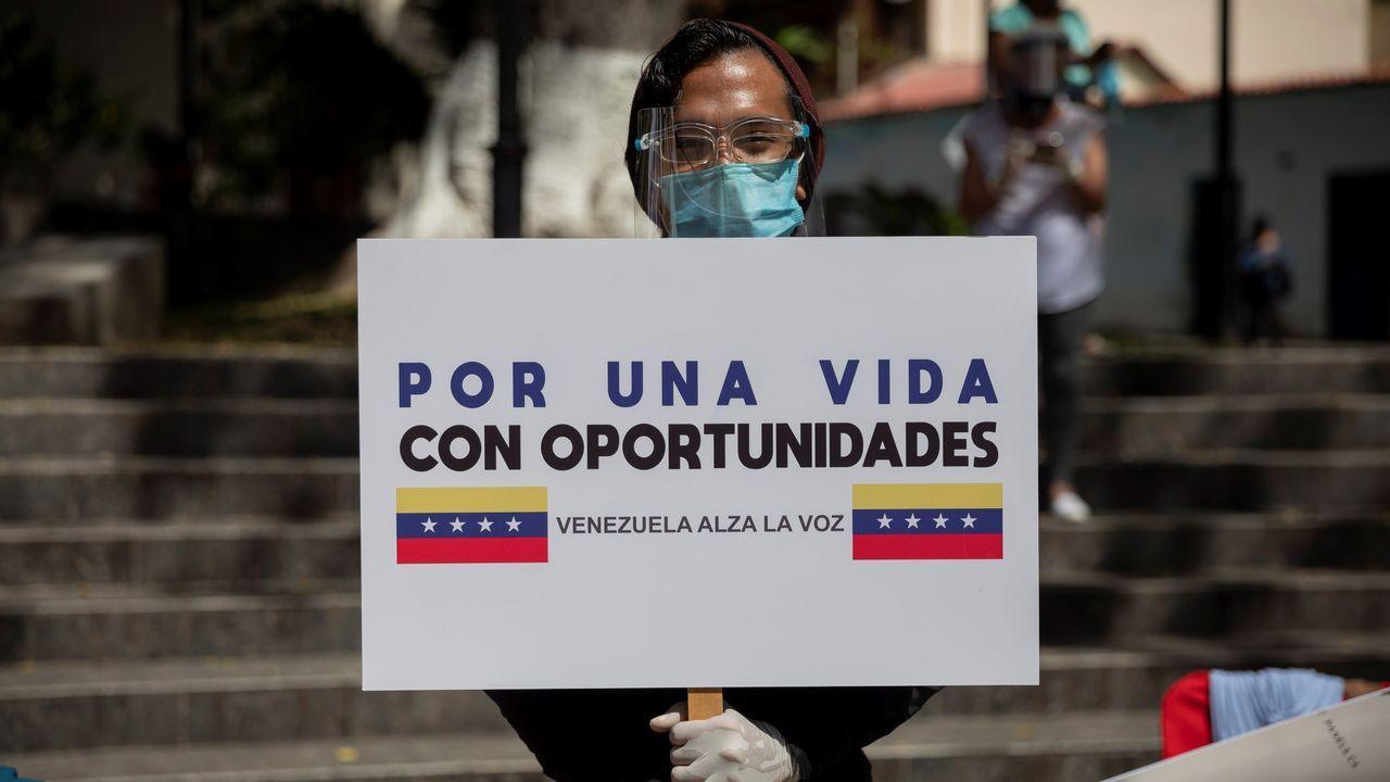 Un hombre sostiene un cartel el sábado, durante la votación presencial de la consulta popular impulsada por Guaidó
