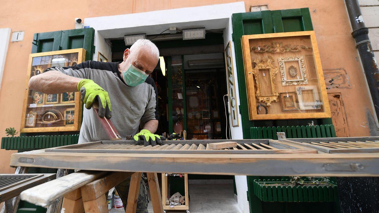 Un trabajador con máscara protectora en un taller de carpintería en la calle Borgo Pio, Roma