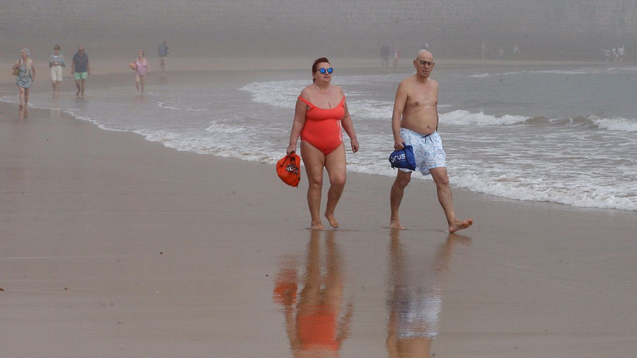 paseo muro de san lorenzo gijon.Un grupo de personas pasea por la Playa de San Lorenzo en Gijón que este miércoles amaneció cubierta de bruma durante la fase 2 de la desescalada del confinamiento por la pandemia de Covid-19