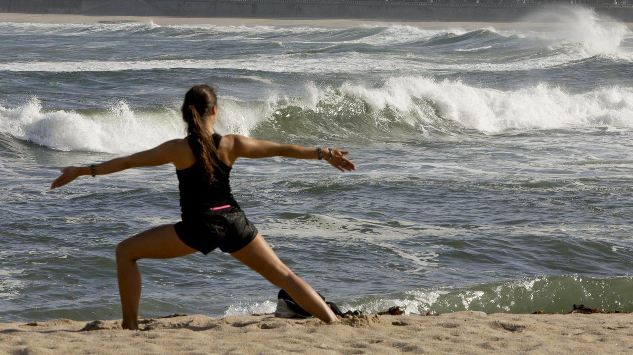 Foto de archivo de una mujer haciendo yoga en la playa