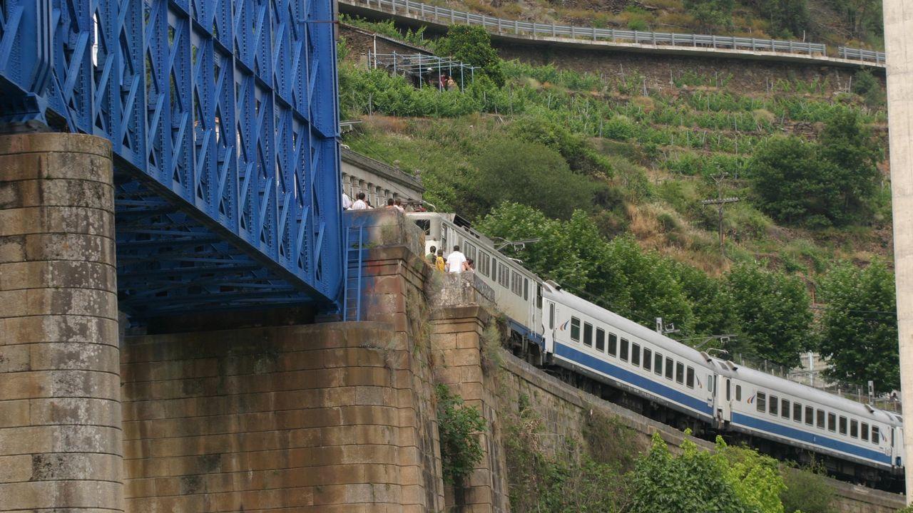 Viajeros del tren Madrid Chamartín-Gijón, durante su transbordo a un Cercanías en la estación de Oviedo