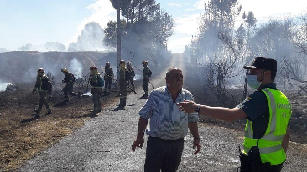 Un guardia civil habla con un vecino de Centulle en la zona afectada por el incendio