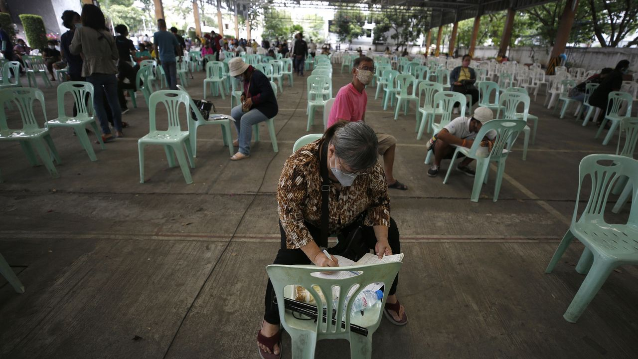Hombres y mujeres esperan en Bangkok para solicitar ayudas del gobierno