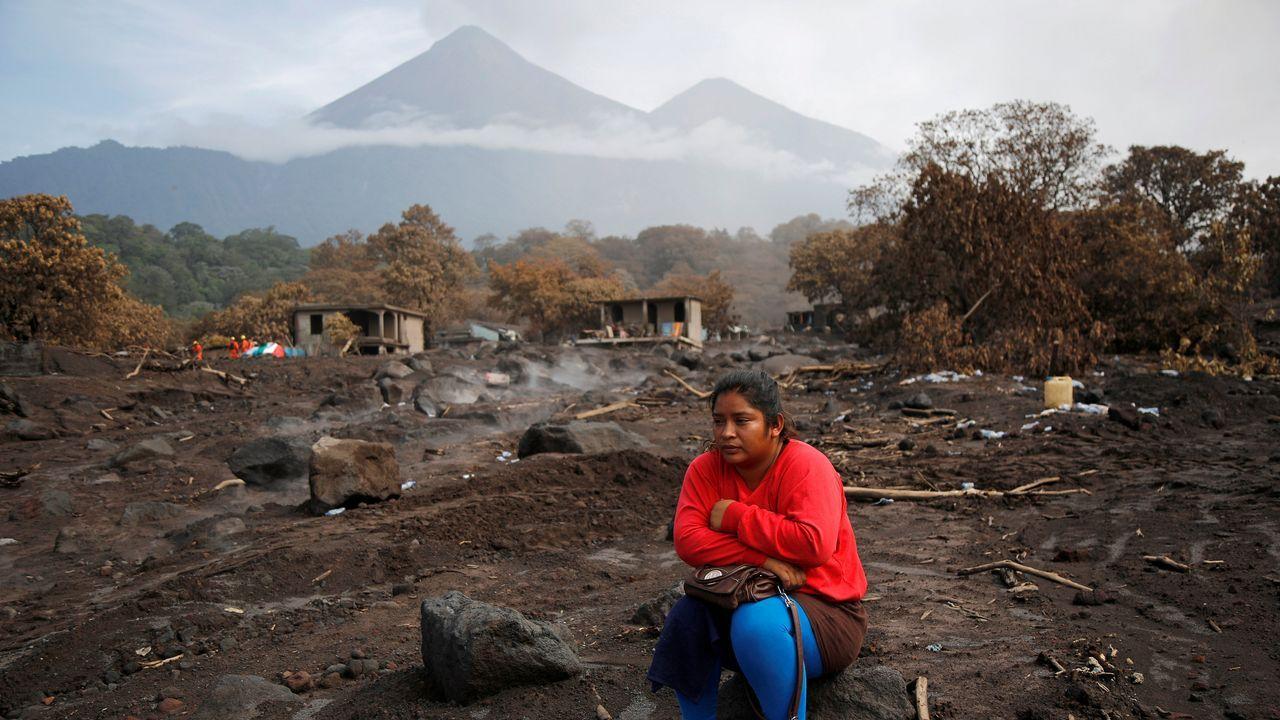 Una mujer observa el lugar donde cree que fueron sepultados sus hermanos, en la zona afecta por la erupción del volcan Fuego, en Guatemala