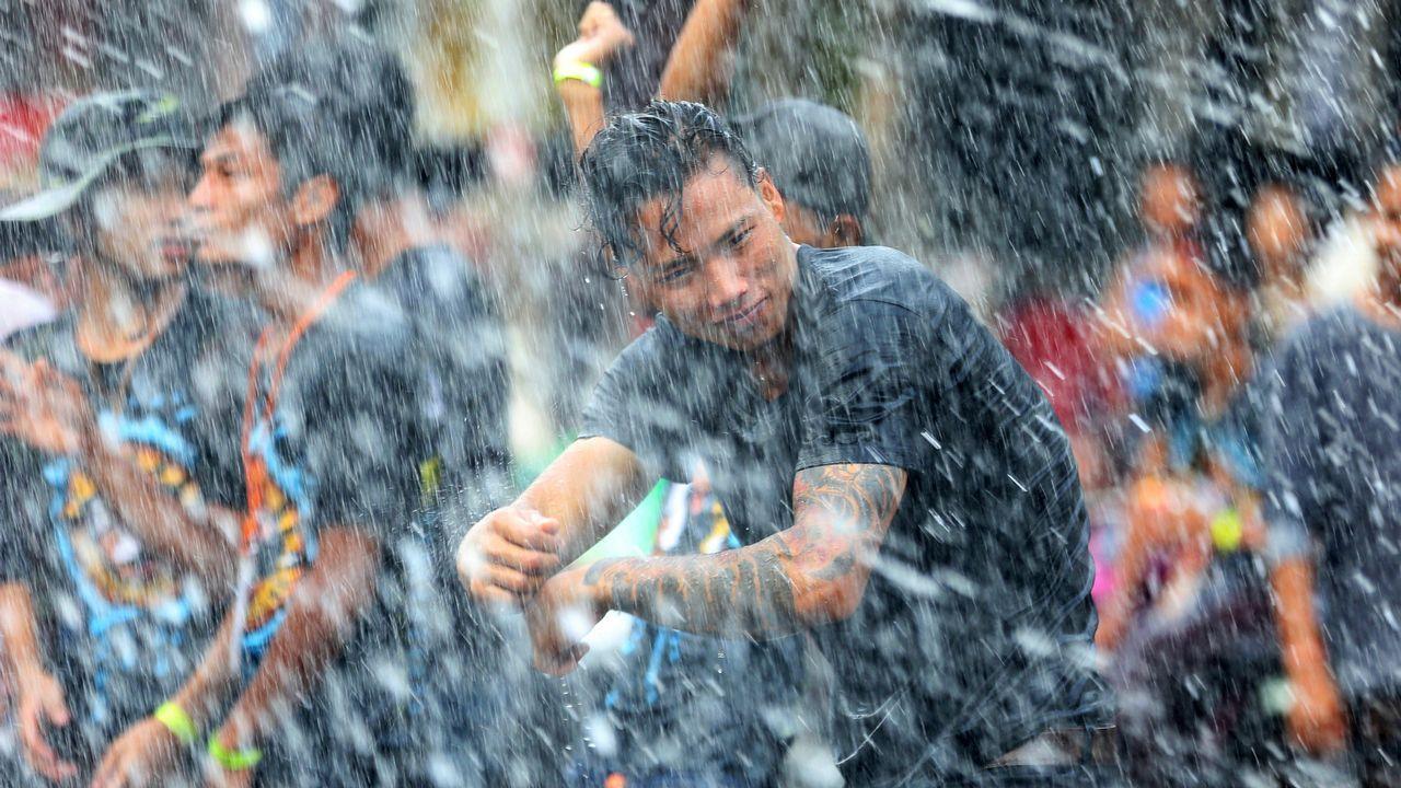 Un hombre baila mientras es salpicado con agua durante las celebraciones del año nuevo birmano, en la localidad de Pyay