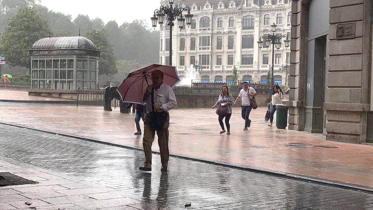 un alumno en un aula, clase, vacía.Los peatones se protegen de las lluviosas tormentas de verano que cayeron sobre Oviedo