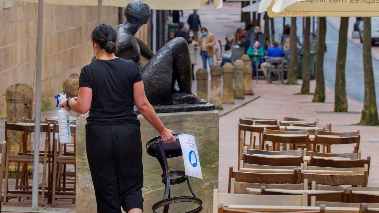 Una mujer desinfecta un asiento de una terraza del centro de Oviedo