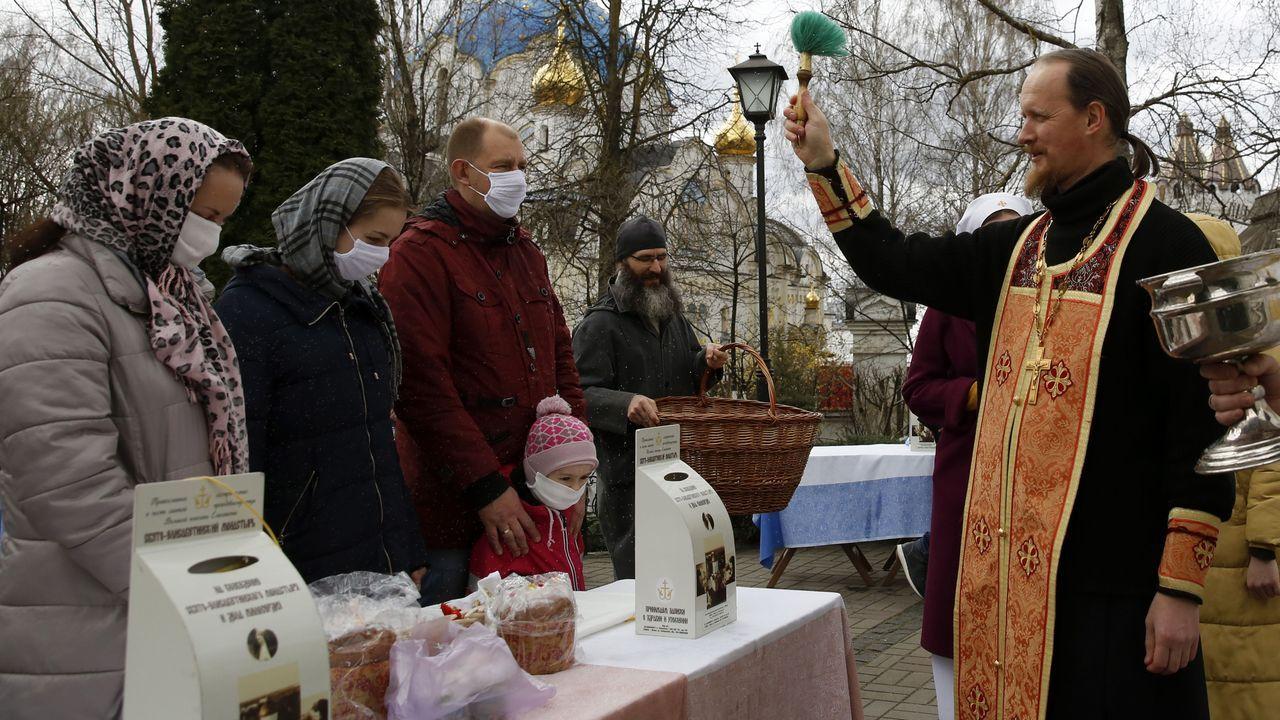 Un sacerdote ortodoxo bendice a los hermanos y sus canastas llenas de comida en la víspera de la Pascua en un convento en las afueras de Minsk, Bielorrusia.