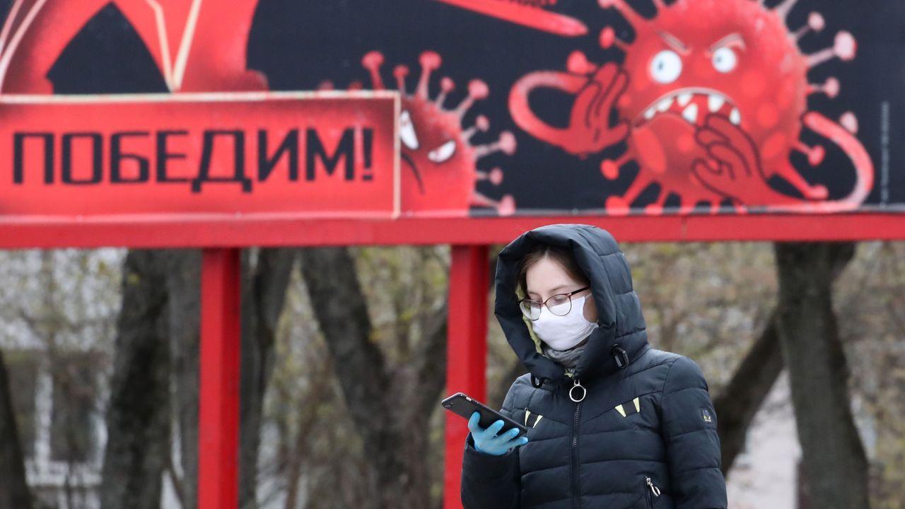 Una mujer camina con una mascarilla y guantes frente a una pancarta que representa el coronavirus y en el que pone  Ganaremos , en Minsk, Bielorrusia