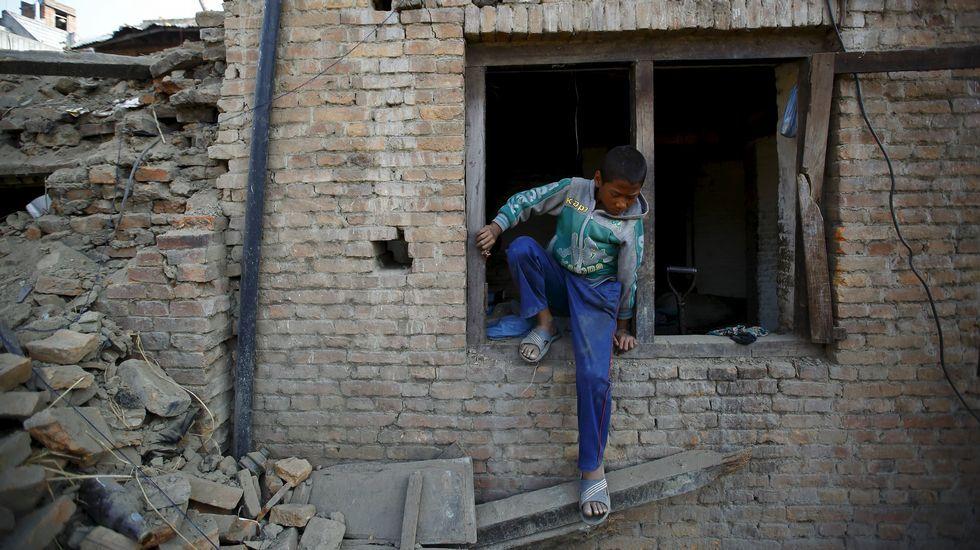 Las dos reinas en el acto de Unicef.Un niño sale por la ventana de su casa en Katmandú.