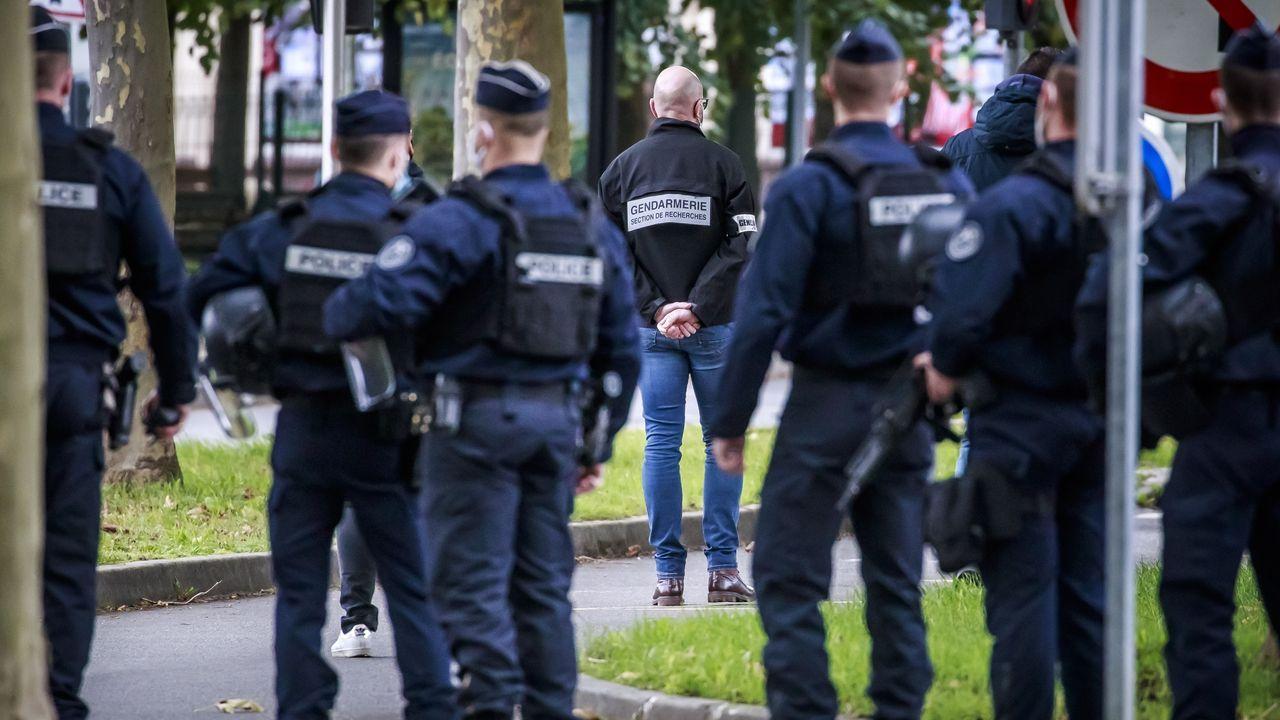 Un policia pasa al lado de un cartel en homenaje al profesor decapitado por un islamista