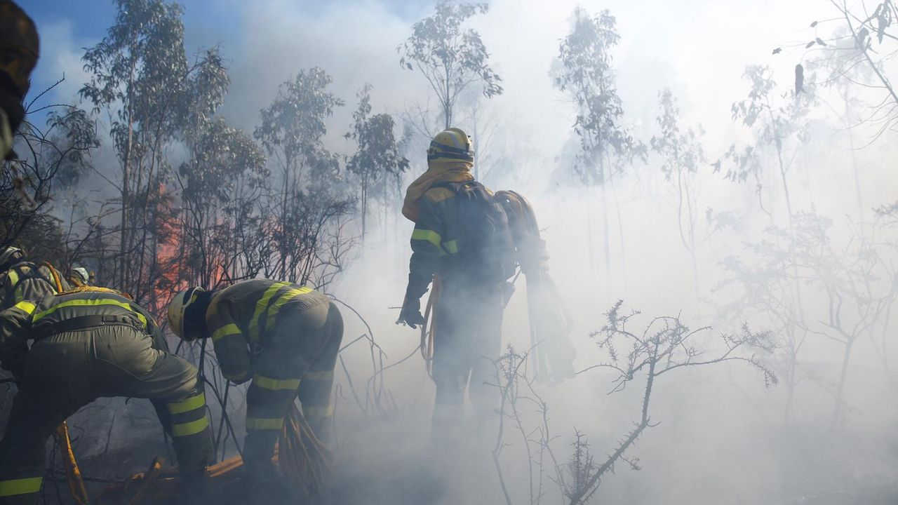 Las llamas devoran el monte en Culleredo.Un avión despegando del aeropuerto de Alvedro