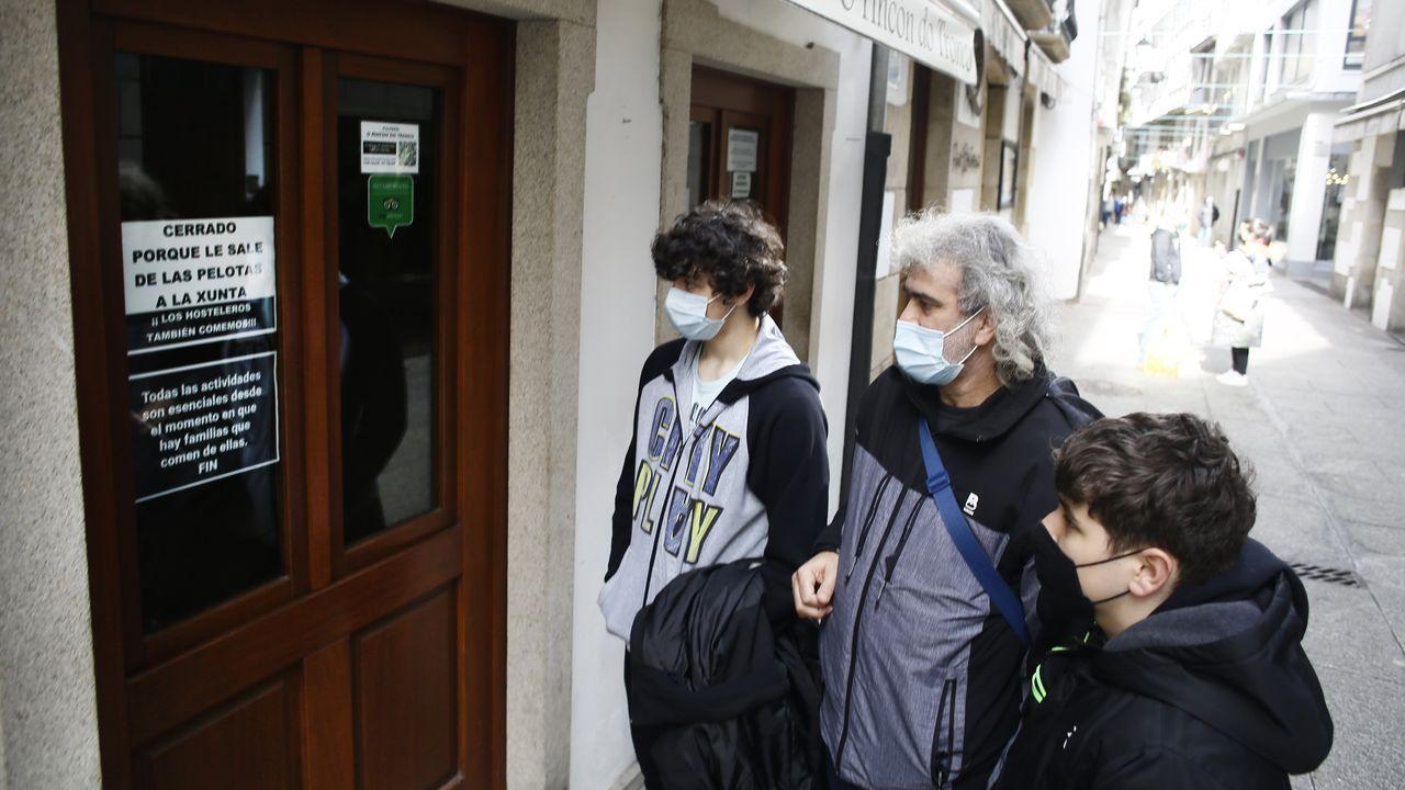 Por los casos de covid-19 en Viveiro, la Xunta decretó el cierre de la hostelería, enojando al sector, que colocó expresivos carteles como el que miraban estos tres vecinos este sábado en un local de la calle Pastor Díaz