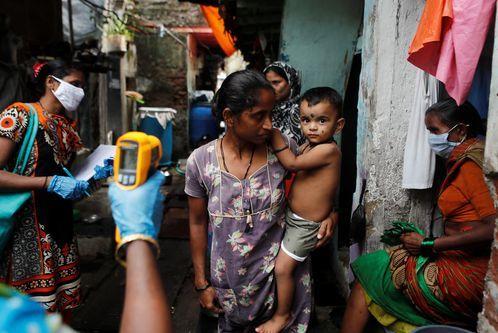 Un sanitario tomando la temperatura a residentes de Mumbai, en la India
