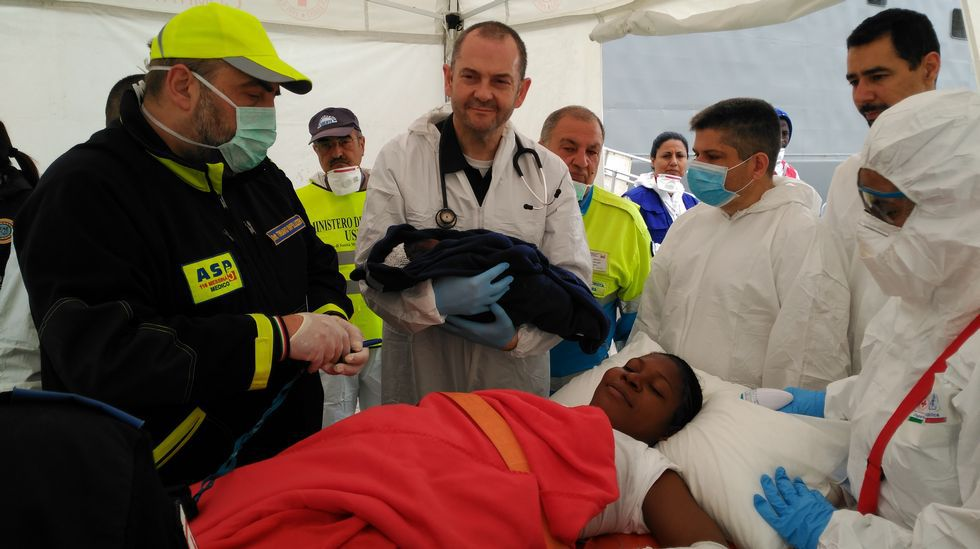 Rescatan a un inmigrante oculto en un tubo de hierro de 40 centímetros de ancho.El marino ferrolano David Díaz, con mascarilla azul, asiste al parto en la fragata «Canarias»