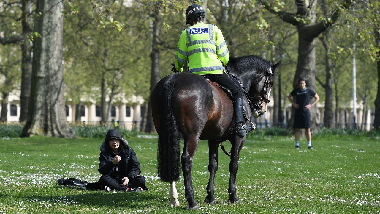 Un policía a caballo conversa con una persona en el parque St James de Londres.