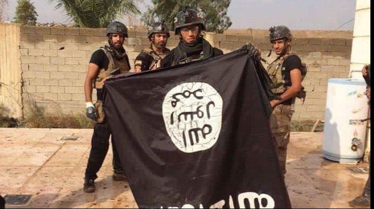 Militares iraquíes sostienen una bandera del Estado Islámico