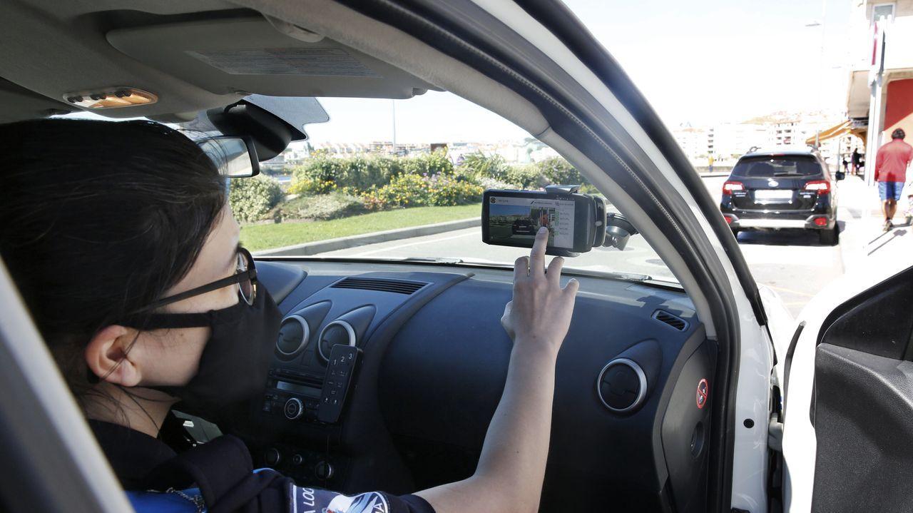 Una policía, este domingo, muestra cómo funciona la aplicación que usan en los controles para saber la procedencia de los vehículos en el puente