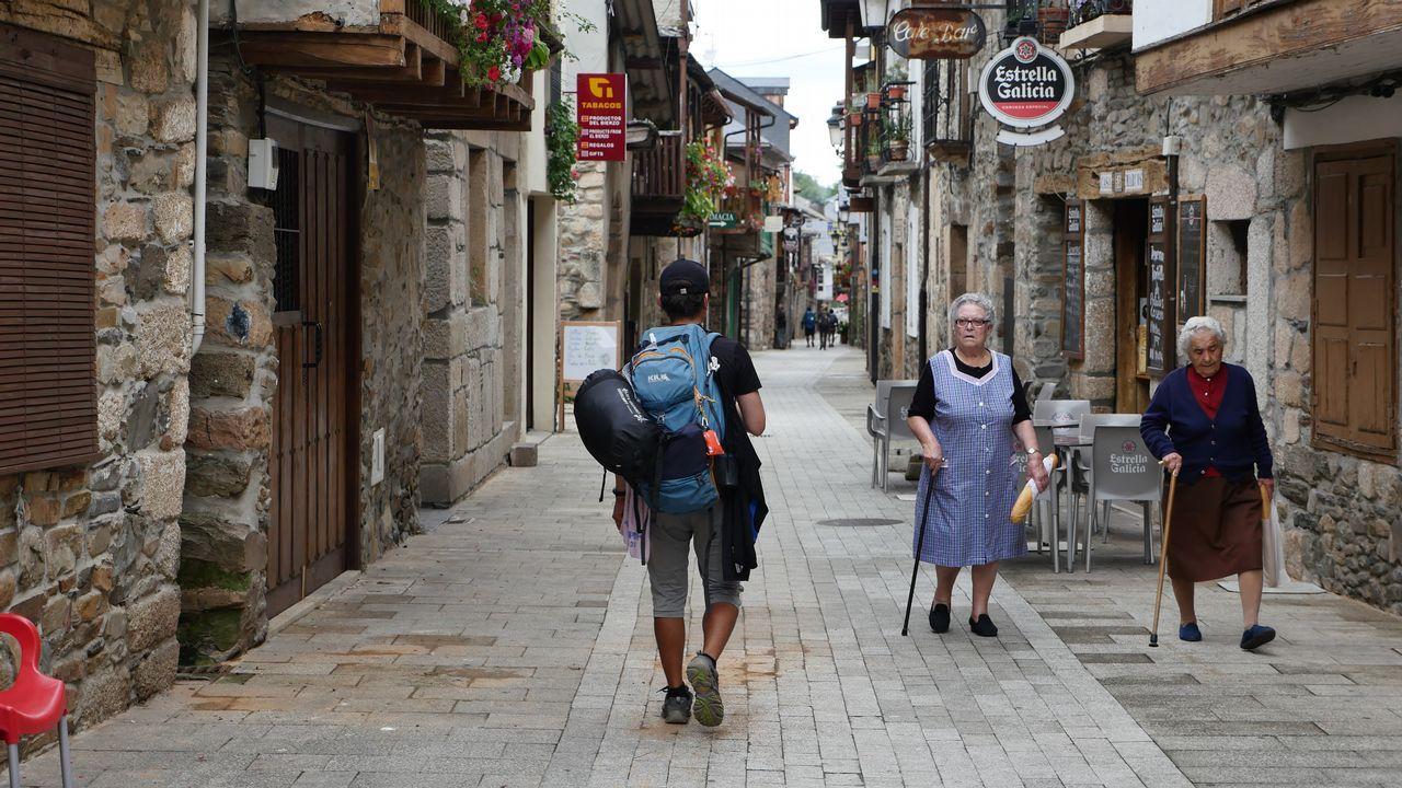 Un peregrino camina por una calle peatonal