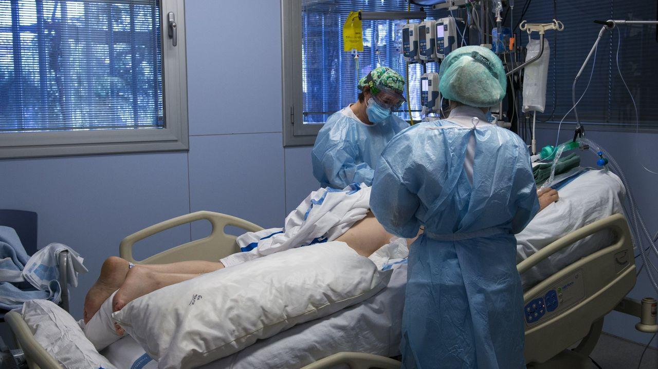 Personal sanitario atendiendo a un paciente ingresado en una Unidad de Cuidados Intensivos para enfermos de coronavirus