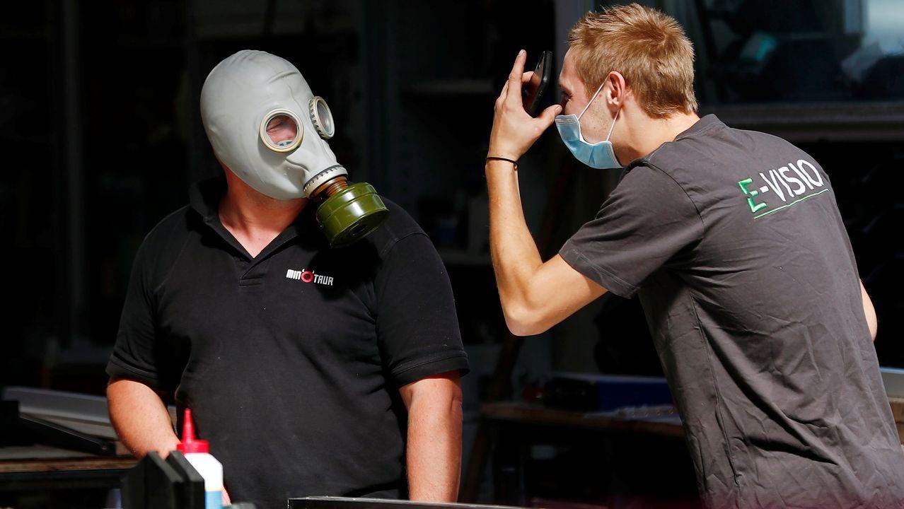 Dos trabajadores charlan. Uno lleva una mascarilla higiénica y el otro una máscara protectora