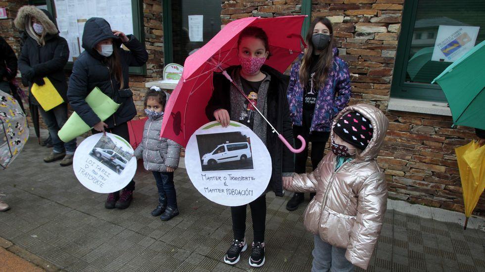 Escolares con carteles en defensa del actual sistema de transporte escolar, del que se encargan los taxistas locales