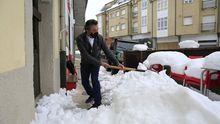 El propietario de la Carnicería Bolaño de O Cadavo retira la nieve decla entrada de su negocio en el que sigue din luz eléctrica