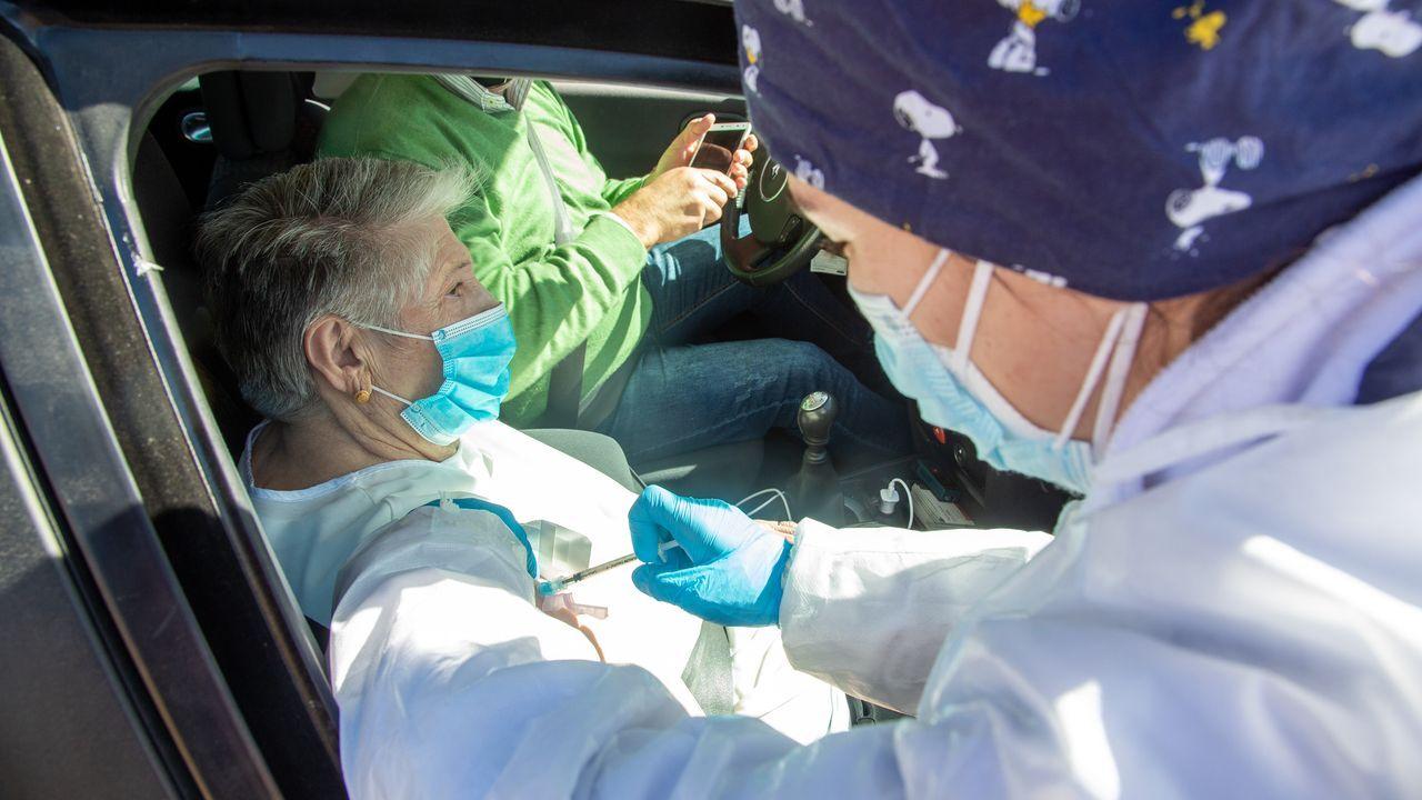 En algunos lugares, se establecieron puntos de vacunación sin bajar del vehículo. En la imagen, una sanitaria inyecta la vacuna a una vecina de Badajoz