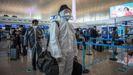 Pasajeros protegidos con plásticos y mascarillas esperan su turno en el aeropuerto de Wuhan en el primer día que se ha levantado el confinamiento en la ciudad