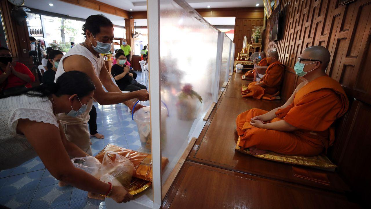 Los monjes budistas tailandeses se han adaptado a la realidad y echan mano de manparas para distanciarse en un acto de ofrenda