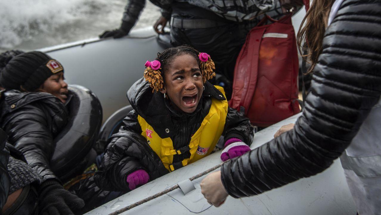 Una niña llora asustada al llegar a la costa de Lesbos desde Turquia