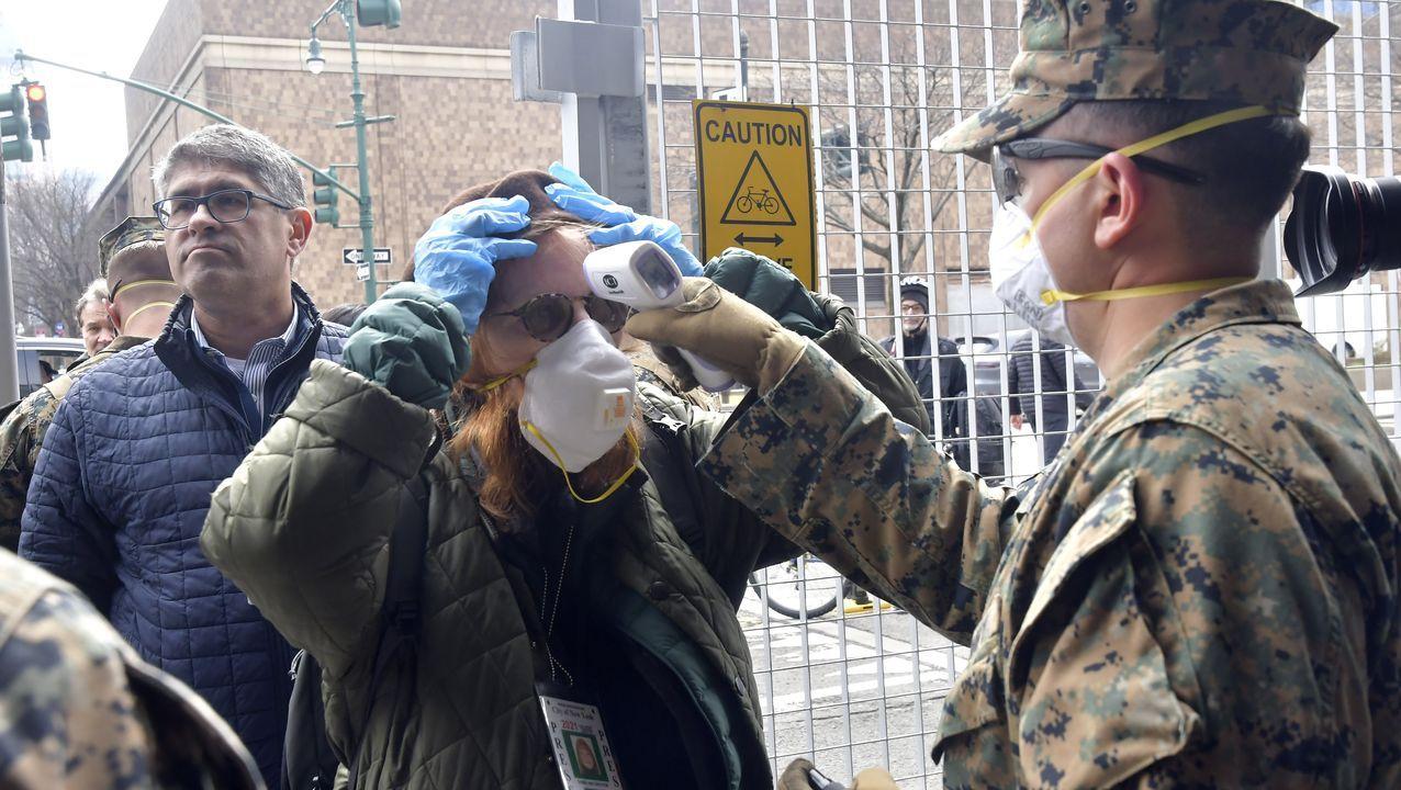 Un marine toma la temperatura a uno de los periodistas que se desplazó al muelle 90 para cubrir el atraque del USNS Comfort