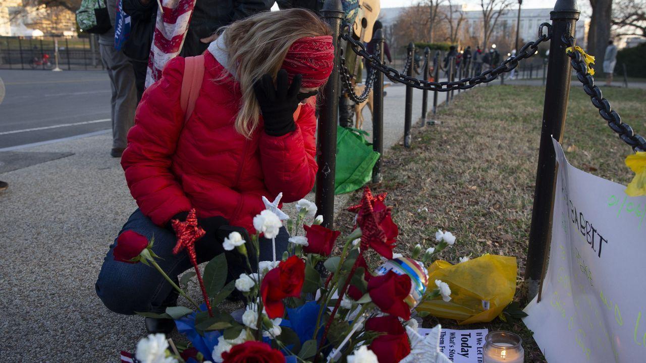 Una mujer deposita flores frente el Capitolio por los muertos durante el asalto