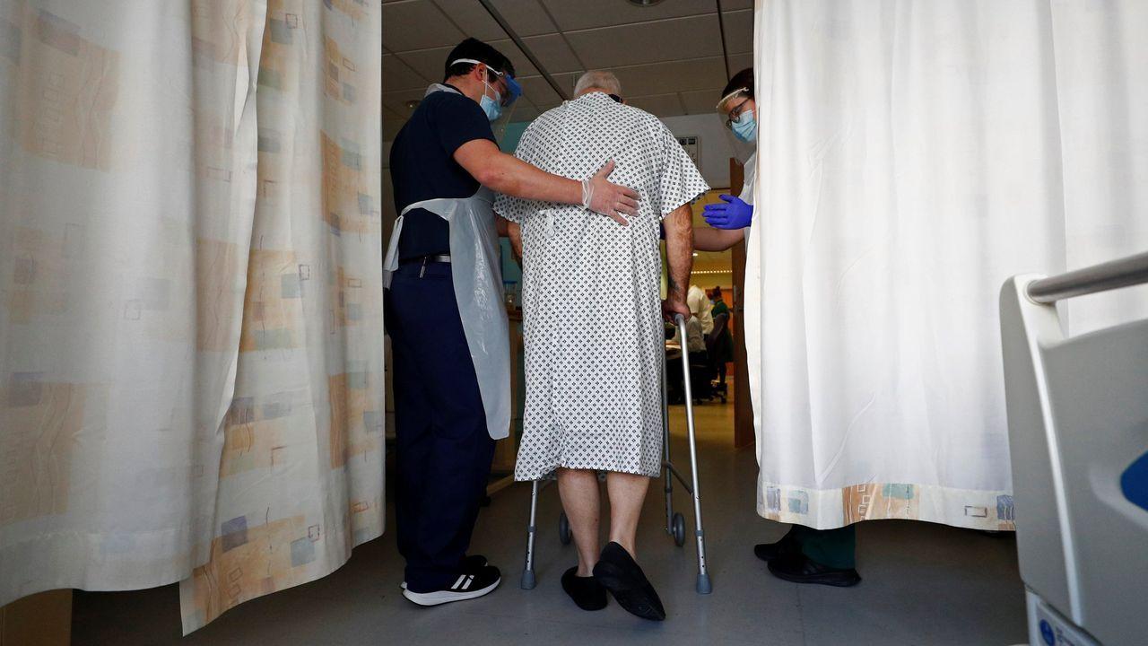 Dos sanitarios ayudan en la recuperación de un paciente del covid-19