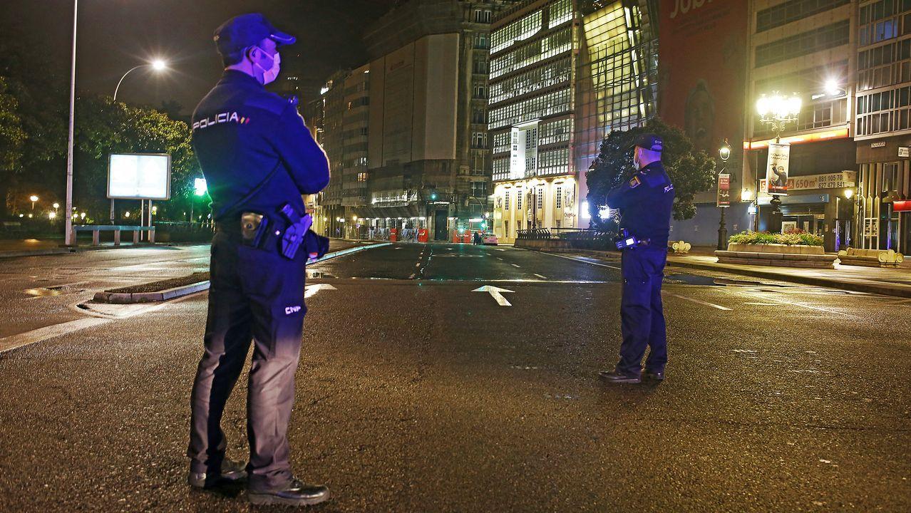 EN ESTADO DE ALARMA. La imagen muestra el aspecto de una de las zonas más céntricas de A Coruña. Es viernes por la noche y todo está desierto. No hay nadie en la calle. Dos agentes de la Policía Nacional vigilan. Su labor es fundamental en estos días de estado de alarma