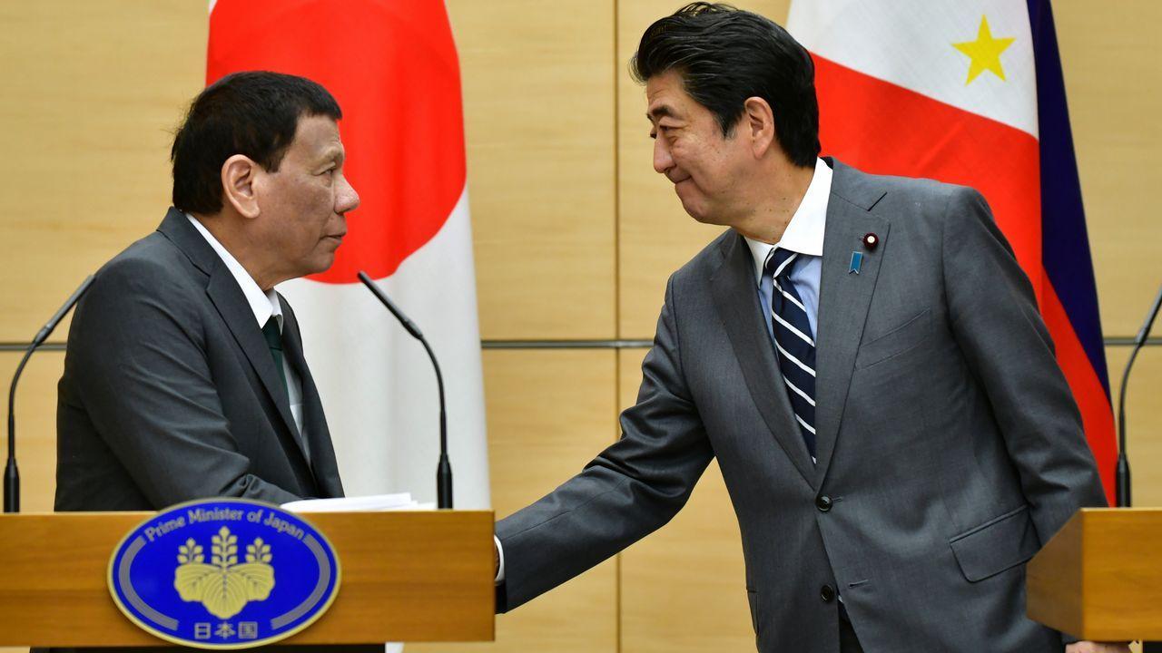 Rodrigo Duterte, a la izquierda, saluda al primer ministro japonés, Shinzo Abe