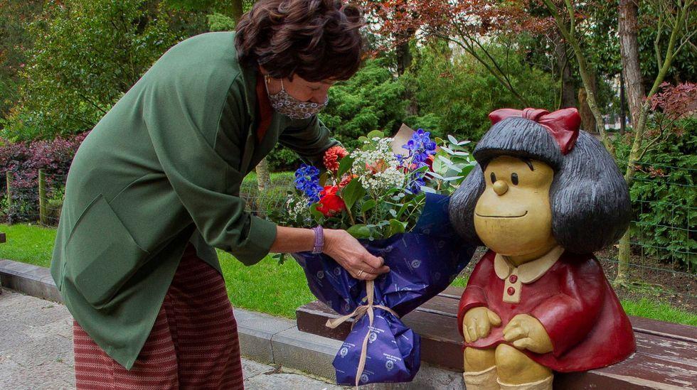 Una mujer pone unas flores junto a la imagen de Mafalda hoy miércoles en el campo San Francisco de Oviedo. EFE.