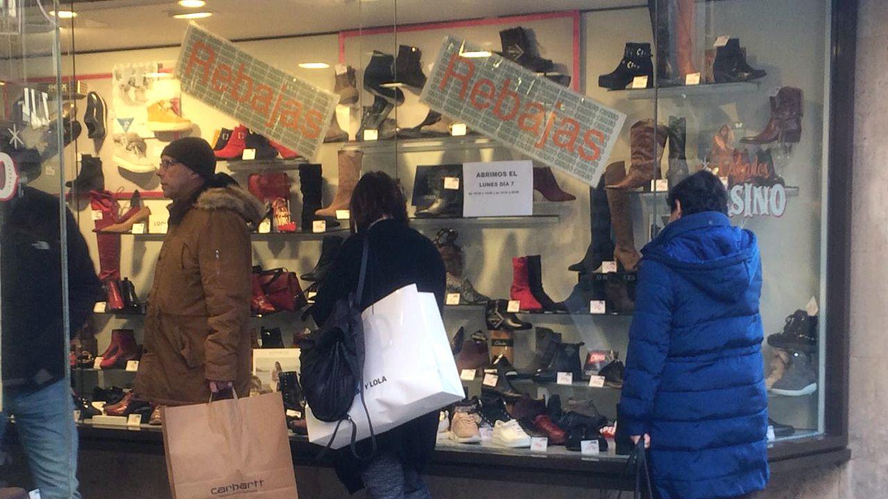 Compradores miran un escaparate con rebajas en el centro de Oviedo