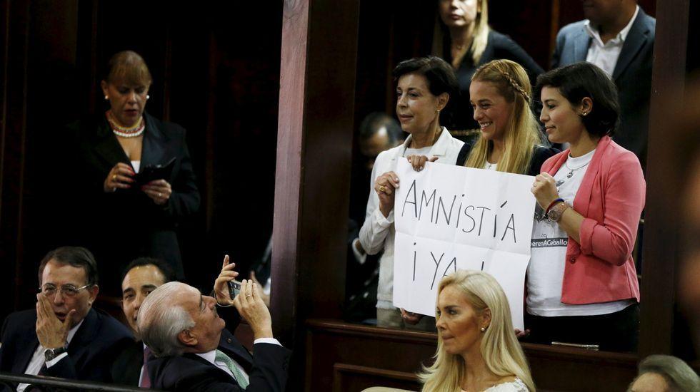 La mujer de Danieal Ceballos, Patricia Ceballos, acompañada de la madre y la mujer de Leopoldo López y sosteniendo un cartel de «Amnistía ¡ya!»