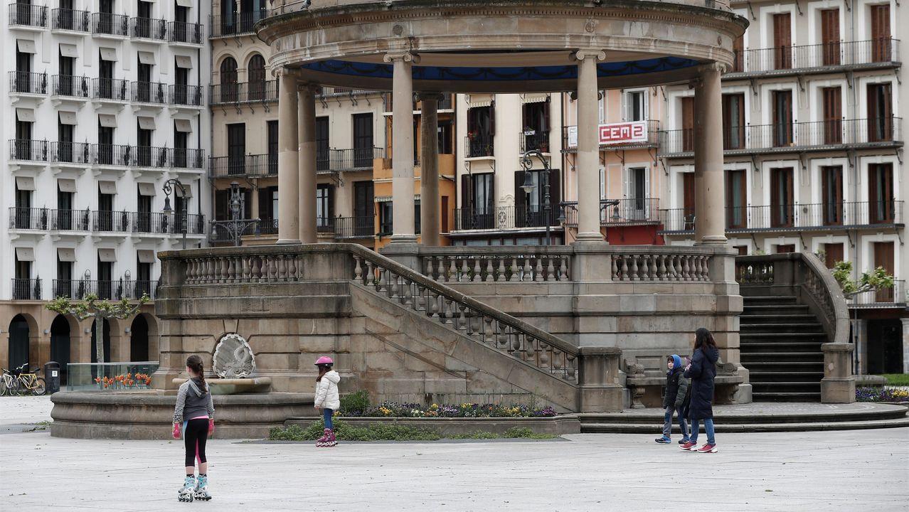 Varios niños acompañados de un adulto juegan en la Plaza del Castillo de Pamplona