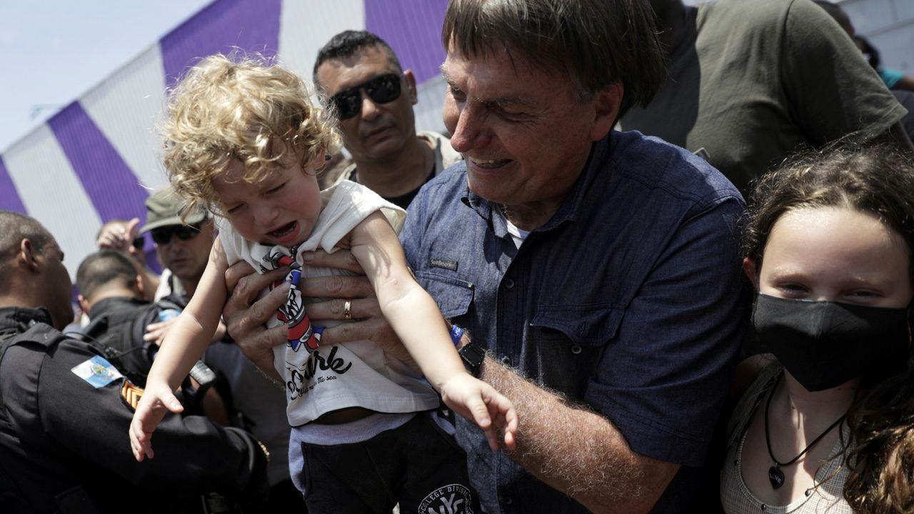 Bolsonaro levanta a un niño tras votar el domingo en Rio de Janeiro