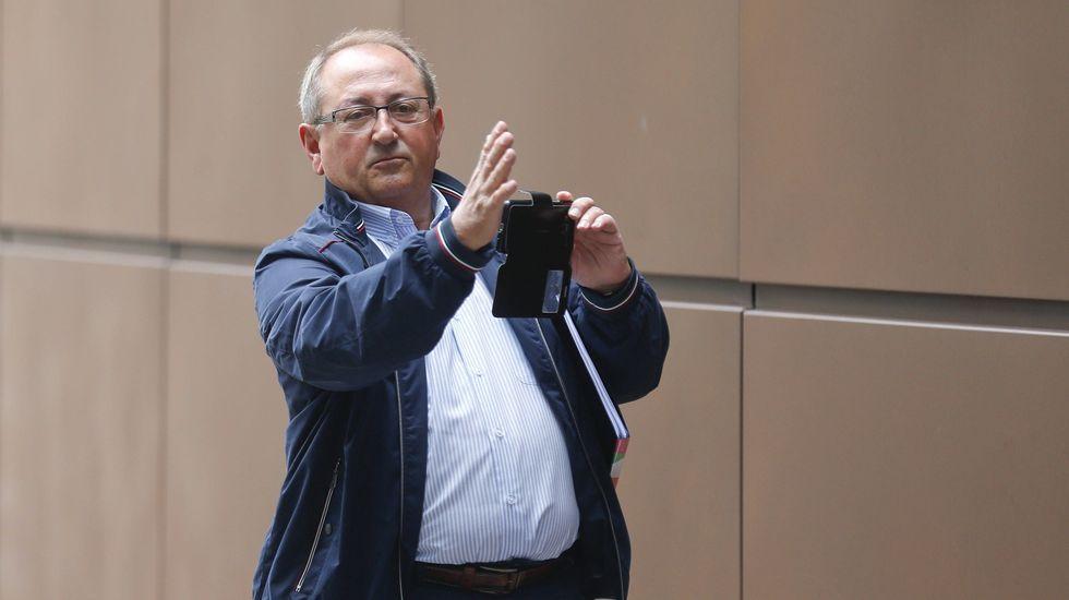 Juan Cigales, excontable del SOMA-UGT y del Infide, fotografía con el móvil a los periodistas a su llegada hoy a la Sección Tercera de la Audiencia Provincial de Oviedo donde ha sido citado como testigo.