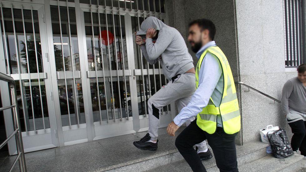 El primer día del gobo de Doade, en fotografías.Uno de los cuatro detenidos se tapa la cara al entrar esposado en el juzgado de Chantada, custodiado por un guardia civil de paisano